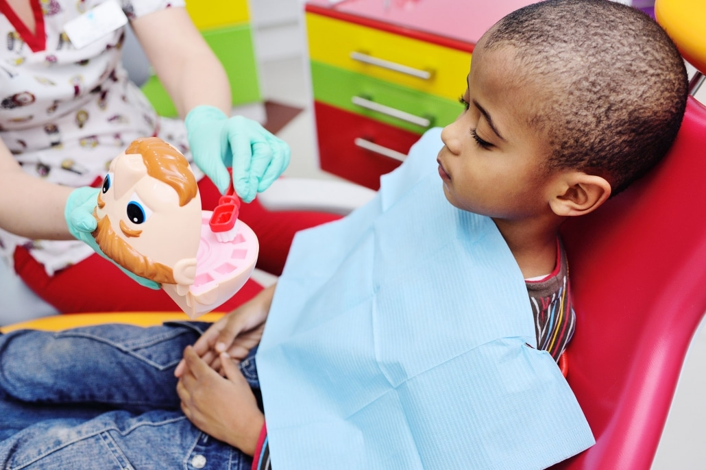 Pediatric Dentist in Beaumont teaching little boy about brushing teeth